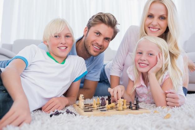 Lächelnde familie, die zusammen schach spielt