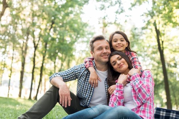 Lächelnde familie, die zusammen zeit im park verbringt