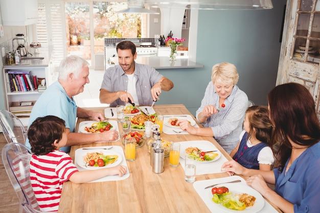 Lächelnde familie mit den großeltern, die am speisetische sich besprechen