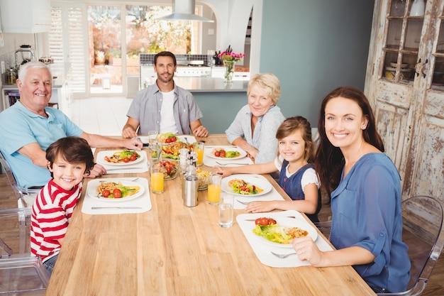 Lächelnde familie mit den großeltern, die am speisetische sitzen