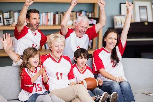 Lächelnde familie mit den großeltern, die match des amerikanischen fußballs aufpassen