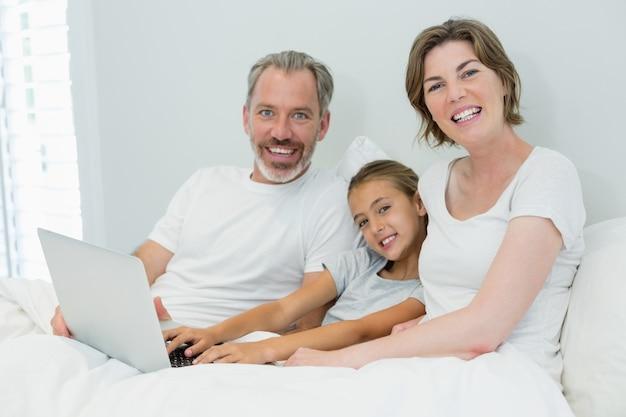 Lächelnde familie mit laptop auf bett im schlafzimmer zu hause