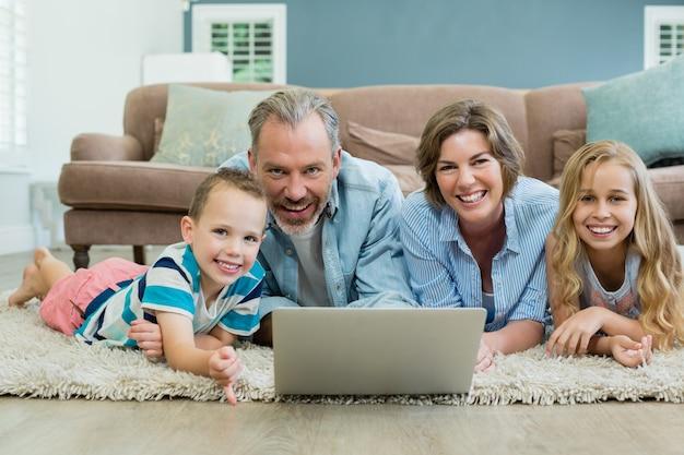 Lächelnde familie mit laptop beim liegen auf teppich im wohnzimmer