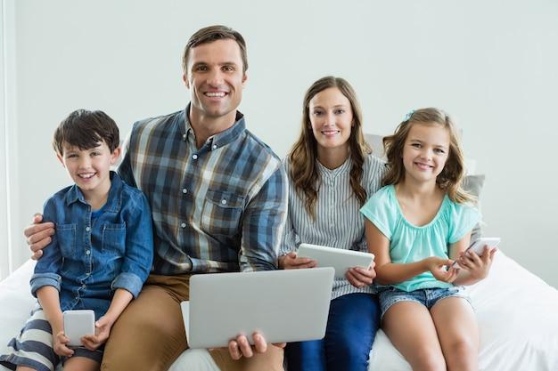 Lächelnde familie mit laptop, digitalem tablet und handy im schlafzimmer