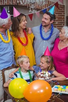 Lächelnde familie mit mehreren generationen, die geburtstag feiert