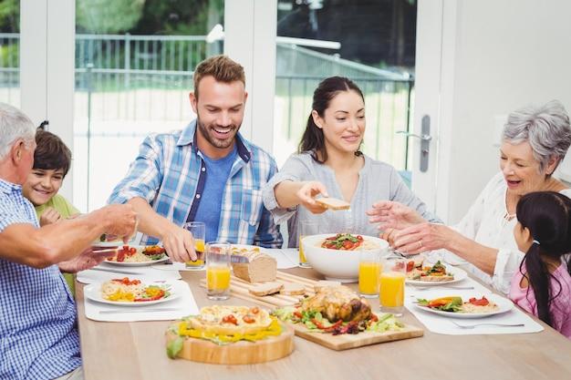 Lächelnde familie mit mehreren generationen, die lebensmittel an speisetische isst