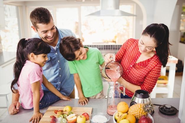 Lächelnde familie mit strömendem fruchtsaft der mutter