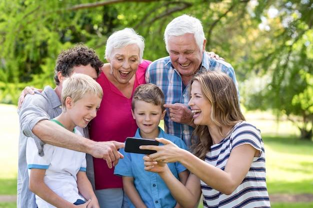Lächelnde familie unter verwendung des smartphone
