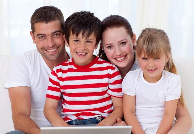 Lächelnde familie zu hause unter verwendung eines laptops