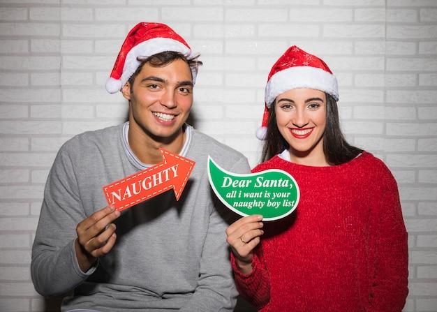 Lächelnde festliche paare mit verschiedenen weihnachtszeichen
