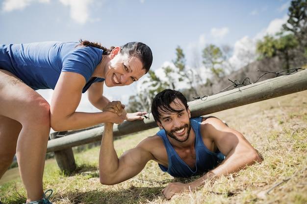 Lächelnde fit frau, die mann hilft, unter dem netz während des hindernislaufs im bootcamp zu kriechen