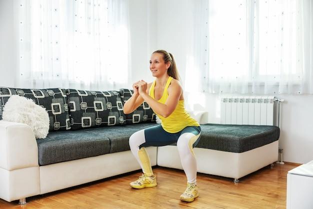 Lächelnde fit-sportlerin, die zu hause kniebeugen macht.