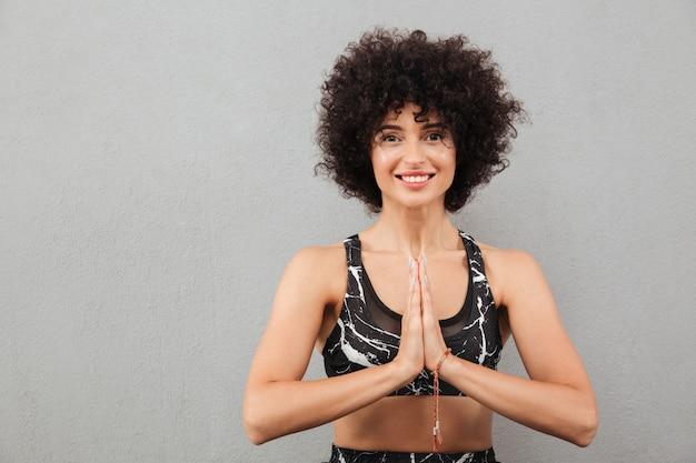Lächelnde fitnessfrau, die hände in der gebetsgeste hält