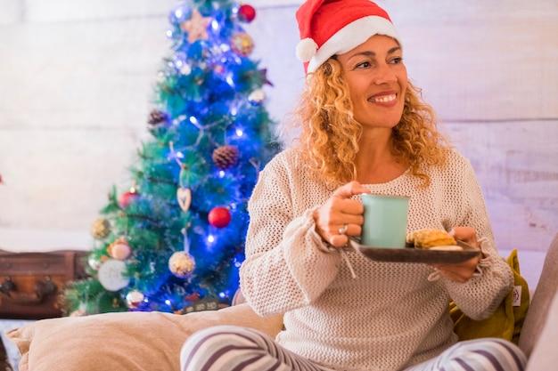 Lächelnde frau allein zu hause, die spaß hat, sitzt auf dem sofa und hält eine tasse tee oder kaffee und kekse auf ihrer hand mit einem weihnachtsbaum im hintergrund