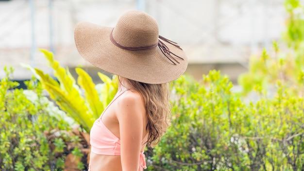 Lächelnde frau am swimmingpool, am tragenden strohhut und an der schwimmenabnutzung