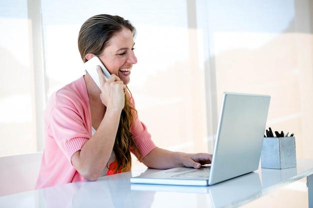 Lächelnde frau an ihrem schreibtisch, auf ihrem laptop und smartphone