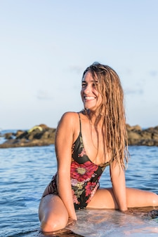 Lächelnde frau auf dem surfbrett, das weg schaut