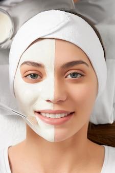 Lächelnde frau auf reinigendem gesicht in kosmetikerin