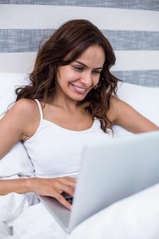 Lächelnde frau bei der anwendung des laptops auf bett