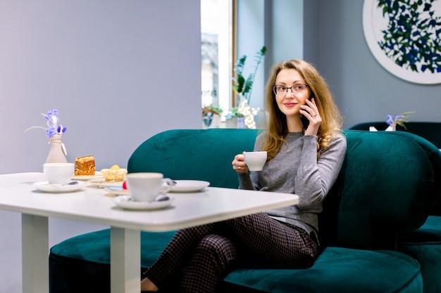 Lächelnde frau bei der unterhaltung an ihrem telefon und essen des kuchens und des trinkenden kaffees am zuhause café, wartend auf ihre freunde