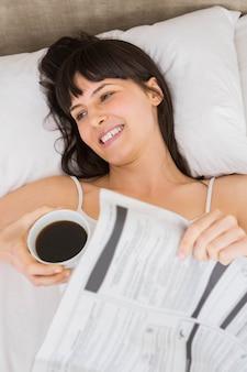 Lächelnde frau beim lügen auf bett mit tasse kaffee
