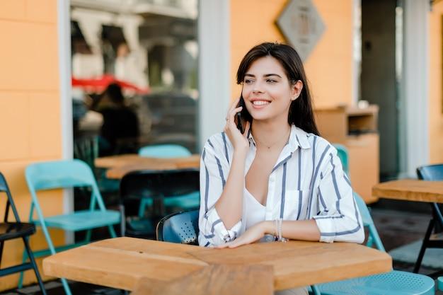 Lächelnde frau benutzt das telefon, das im café sitzt