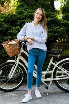 Lächelnde frau der vorderansicht mit fahrrad