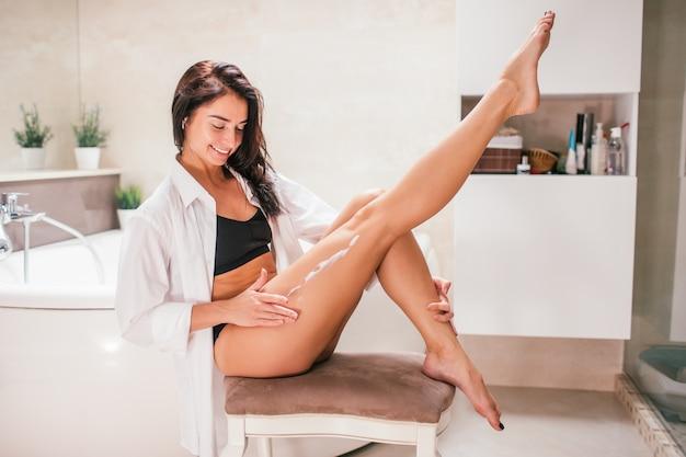 Lächelnde frau des jungen dünnen brunette, die körperlotion auf dem bein sitzt auf einem stuhl in einem badezimmer anwendet. sostnes und hautpflegekonzept.