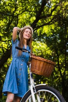 Lächelnde frau des niedrigen winkels mit fahrrad