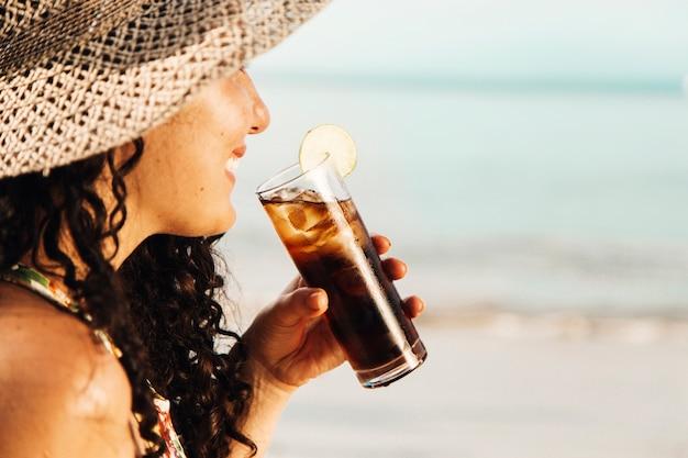 Lächelnde frau, die abkühlendes getränk trinkt