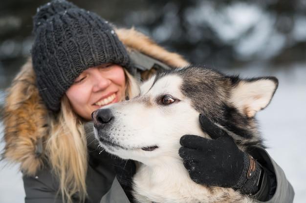 Lächelnde frau, die alaskisches malamute mit liebe im winterwald umarmt