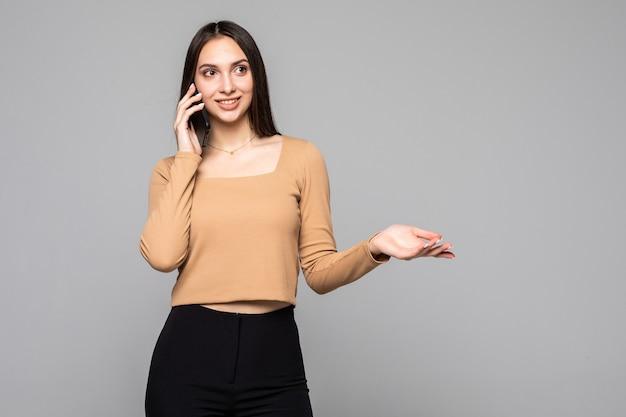 Lächelnde frau, die am smartphone spricht, isoliert auf einer grauen wand