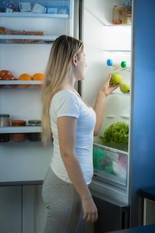 Lächelnde frau, die am späten abend am offenen kühlschrank posiert