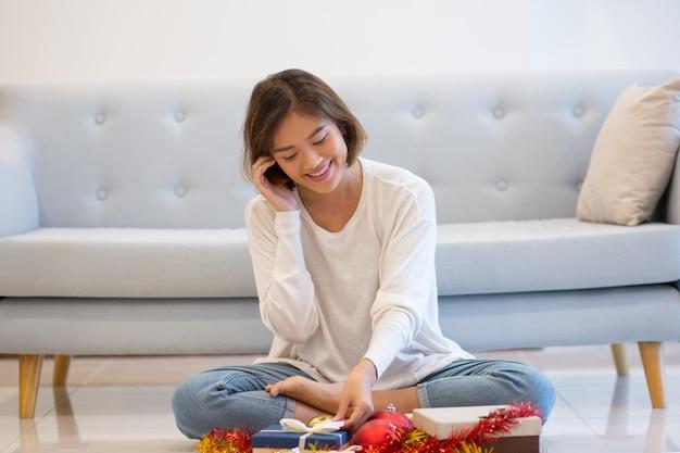 Lächelnde frau, die am telefon spricht und mit weihnachtsgeschenken sitzt