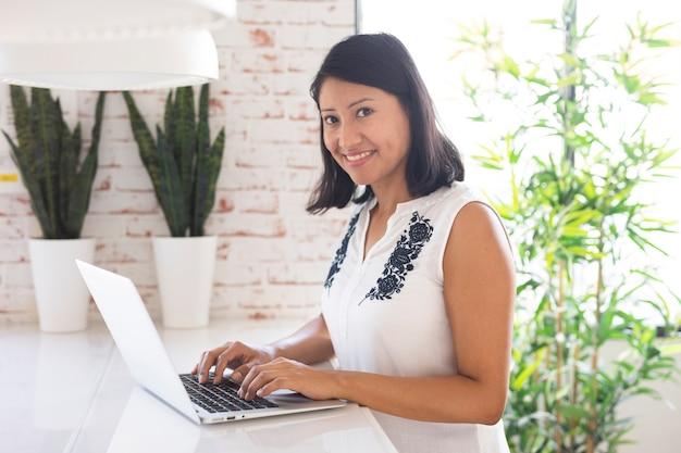 Lächelnde frau, die an laptop arbeitet