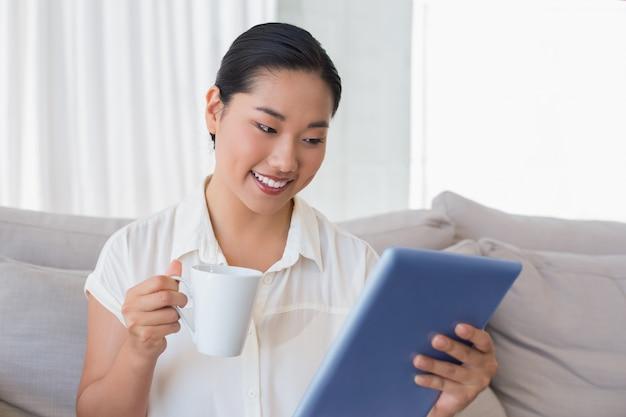 Lächelnde frau, die auf couch unter verwendung des tabletten-pc trinkt kaffee sitzt