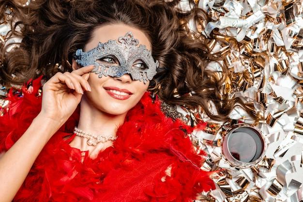 Lächelnde frau, die auf dem boden unter der goldenen lamettanahaufnahme liegt, die eine karnevalsmaske nahe bei einem glas rotwein trägt