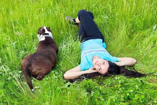 Lächelnde frau, die auf dem gras mit hund liegt