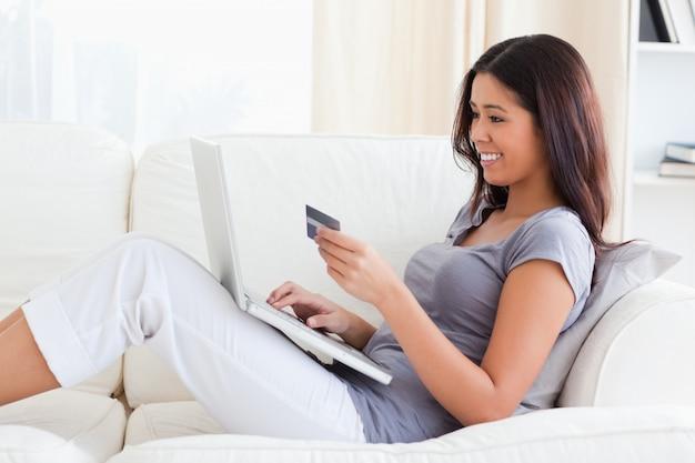 Lächelnde frau, die auf dem sofa hält kreditkarte sitzt
