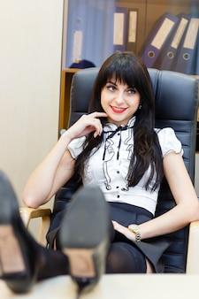 Lächelnde frau, die auf dem tisch in einem büro an einem schreibtisch mit seinen beinen sitzt