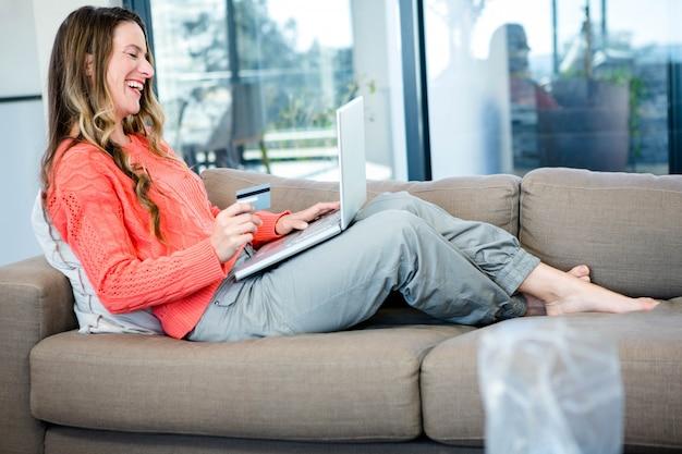 Lächelnde frau, die auf der couch auf ihrem laptop mit ihrer kreditkarte liegt
