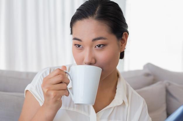 Lächelnde frau, die auf der couch trinkt kaffee sitzt