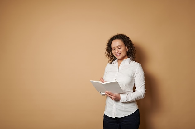 Lächelnde frau, die auf einem beigen hintergrund steht und notizen macht, während sie ein buch liest