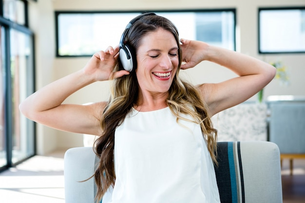 Lächelnde frau, die auf einer couch hört musik durch ihre heaphones sitzt