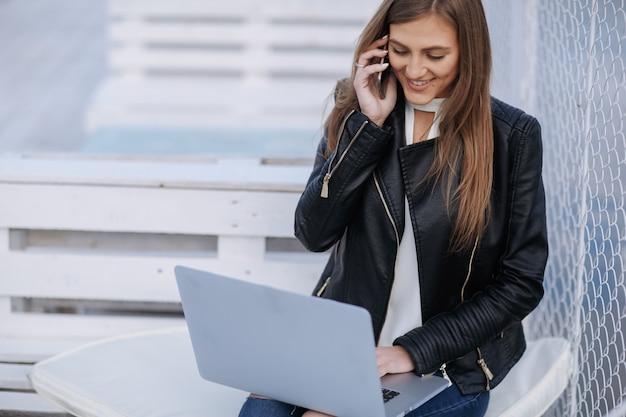 Lächelnde frau, die auf einer weißen bank sitzt auf ihrem telefon sprechen