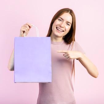 Lächelnde frau, die auf einkaufstasche zeigt