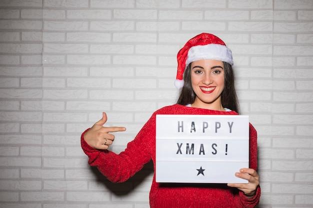 Lächelnde frau, die auf glückliches weihnachtszeichen zeigt