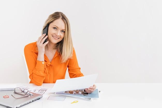 Lächelnde frau, die auf smartphone mit dem halten des weißbuches am arbeitsplatz spricht