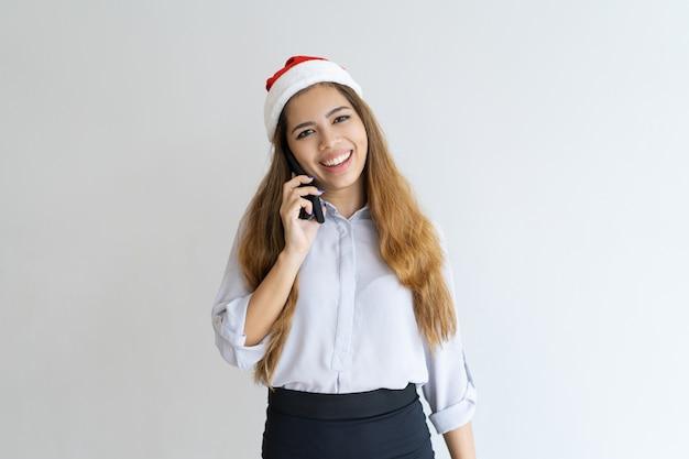 Lächelnde frau, die auf smartphone spricht und santa claus-hut trägt