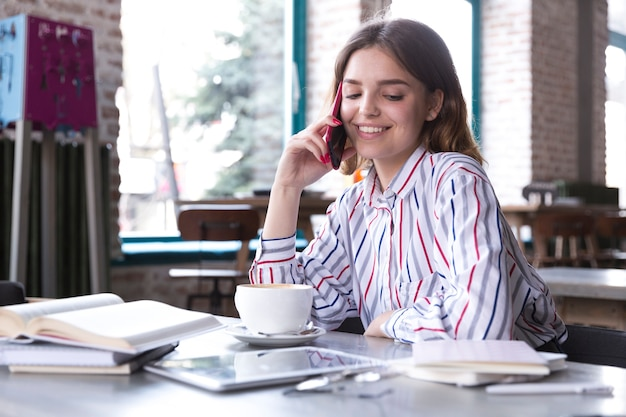 Lächelnde frau, die auf smartphone spricht